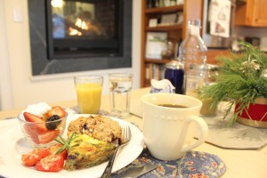 Breakfast of scone, fritata, roasted tomatoes with parmesan, fruit cup, yogurt, coffee, orange Juice in from of hearth