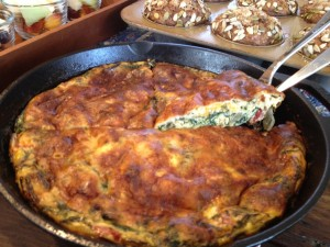 Power greens frittata lifted from a cast iron pan