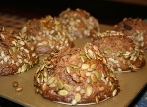 Golden brown muffins with carrots, pineapple, & apple topped with pumpkin seeds in muffin baking pan